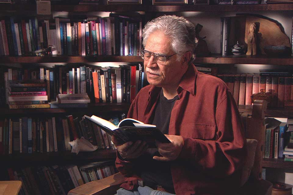 A photograph of Rudollfo Anaya reading a book in his study