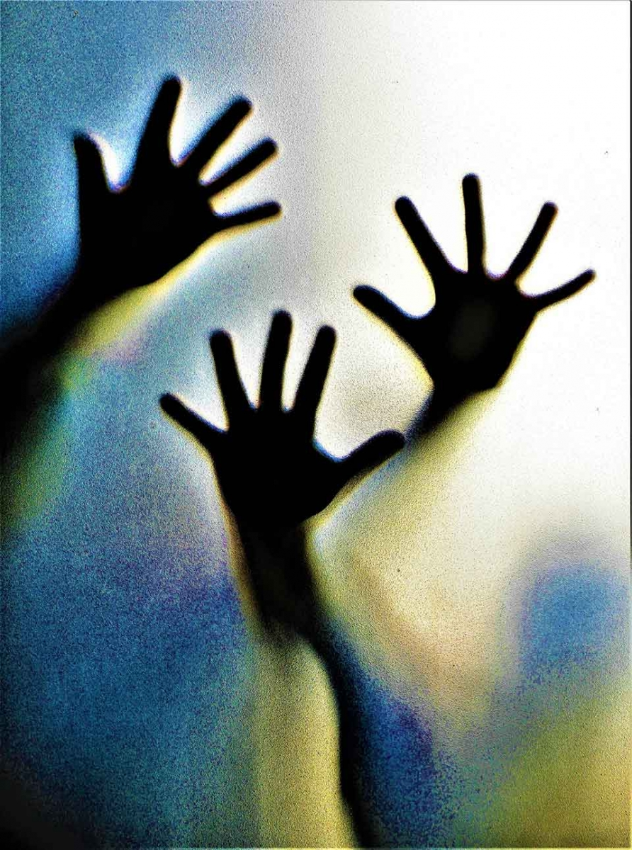 A photograph of hands pressed up against material, backlit by blue and yellow light