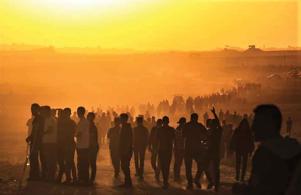 A photograph of a throng of people walking on a dusty landscape at sunset