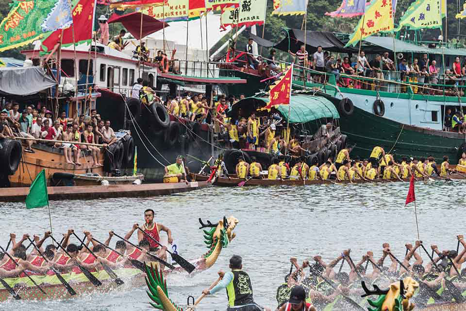 A photograph of a raucous public festival where teams of rowers in dragon boats traverse a river