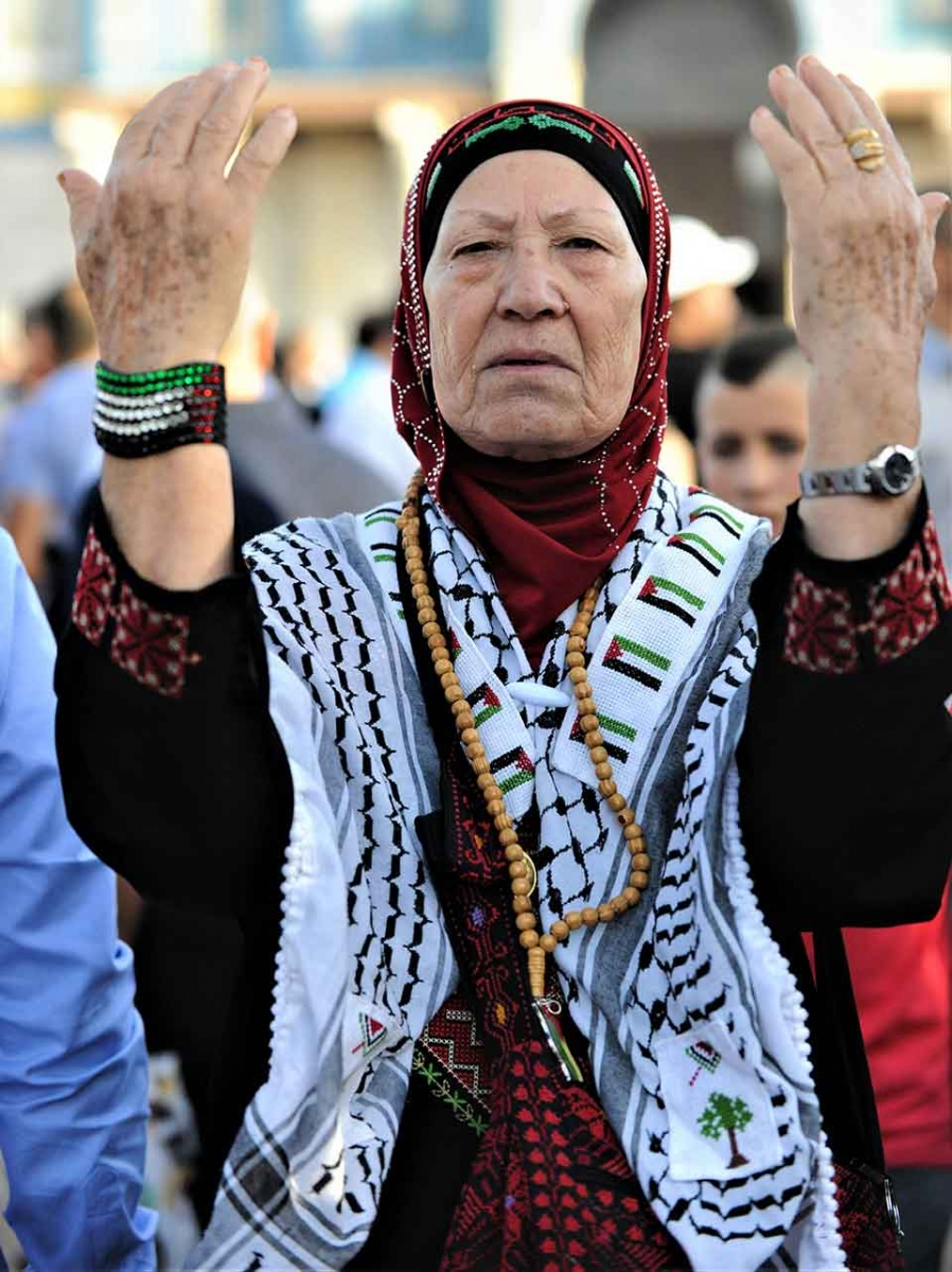 Palestinian woman with upraised hands