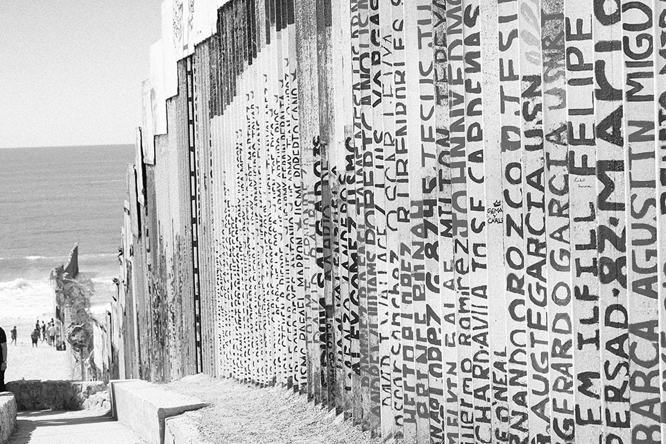 A black and white photograph of a fence made of upright slats, each with words written on them vertically