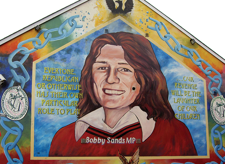"A mural with a painting of Bobby Sands. The text reads ""Everyone. Republican or otherwise has their own particular role to play...our revenge will be the laughter of our children."""