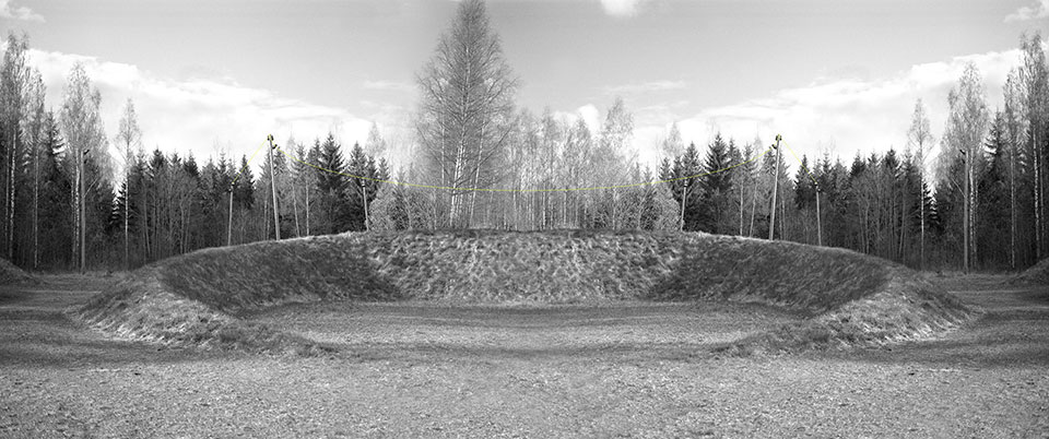 A black and white photograph of a crater, now covered with grass