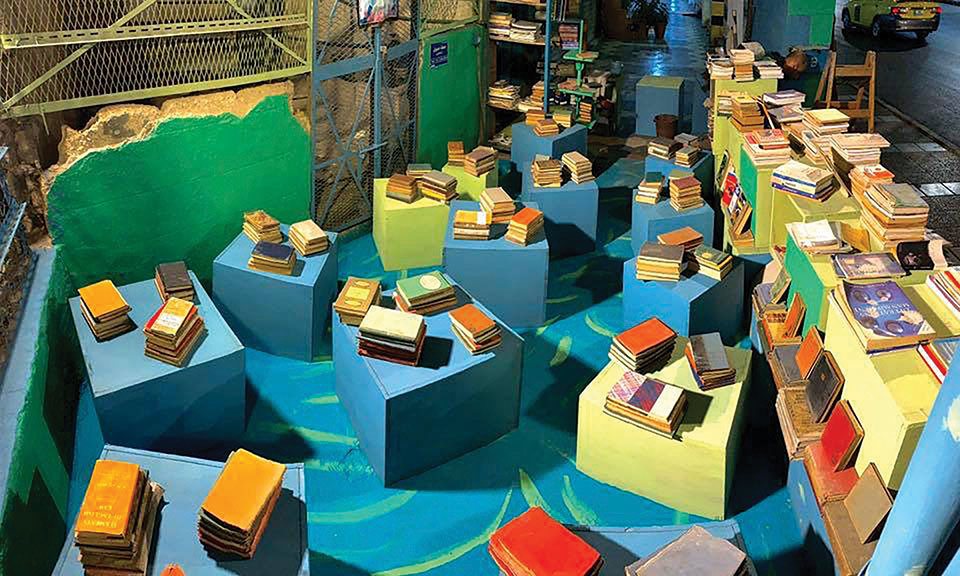 An aerial shot of a warehouse type space, the floor covered with colored boxes with stacks of books on them