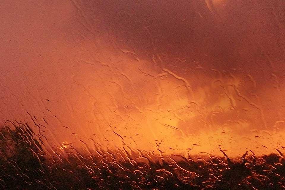 A photograph of a orange hued landscape as seen through a rain-swept window