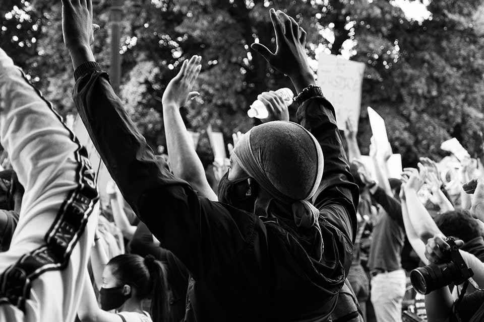 A black and white photo of a masked protestor with his hands up