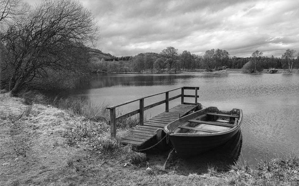 A black and white photo of a small boat tied to a dock at the edge of a wooded pond