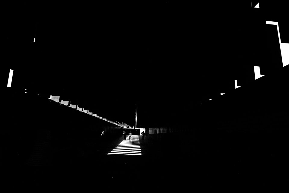 A photograph of the interior of the The National Memorial for Peace and Justice, mostly swallowed in darkness with a small path lit in the center and small slits visible on the walls