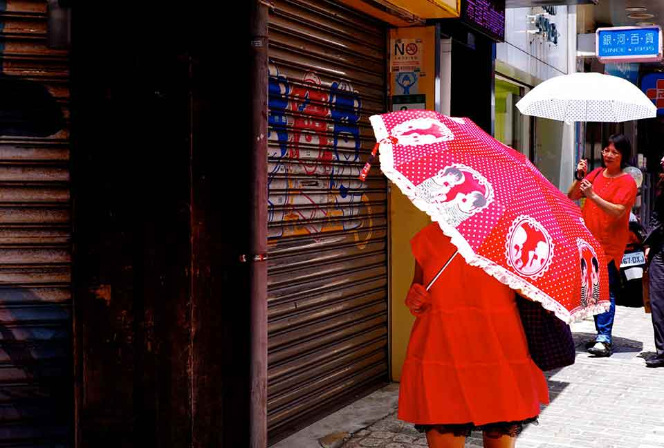 A woman, dressed in red, walks down the street, her face obscured by a red umbrella