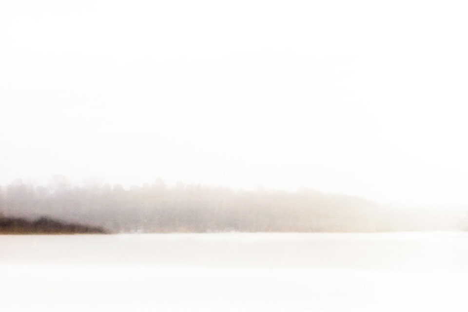 A hazy photo of a snow covered landscape