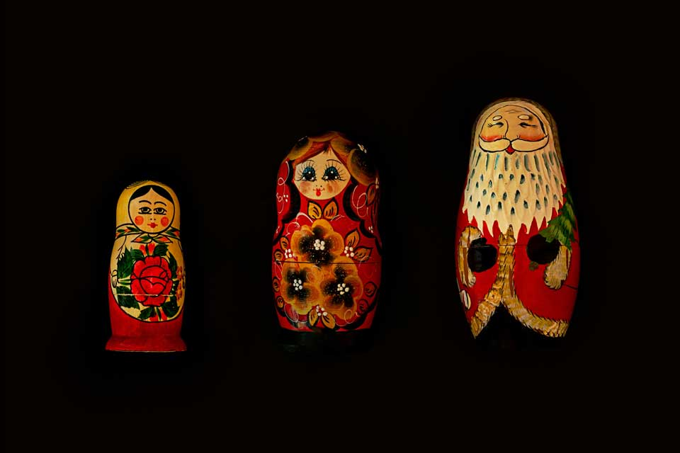 Three Christmas dolls laid side by side against a black background