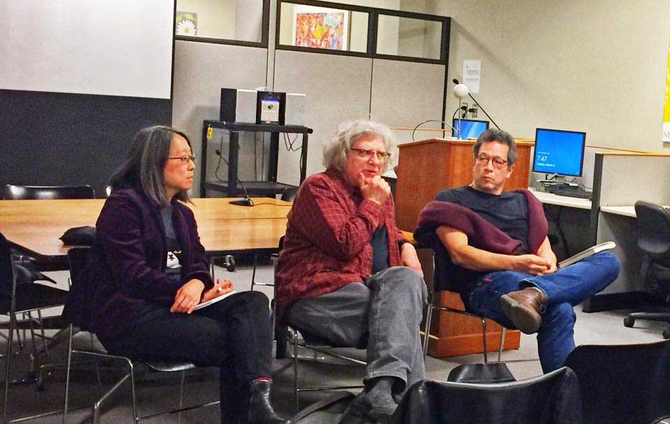 Three people sitting in chairs in conversation with an audience (which is off panel)