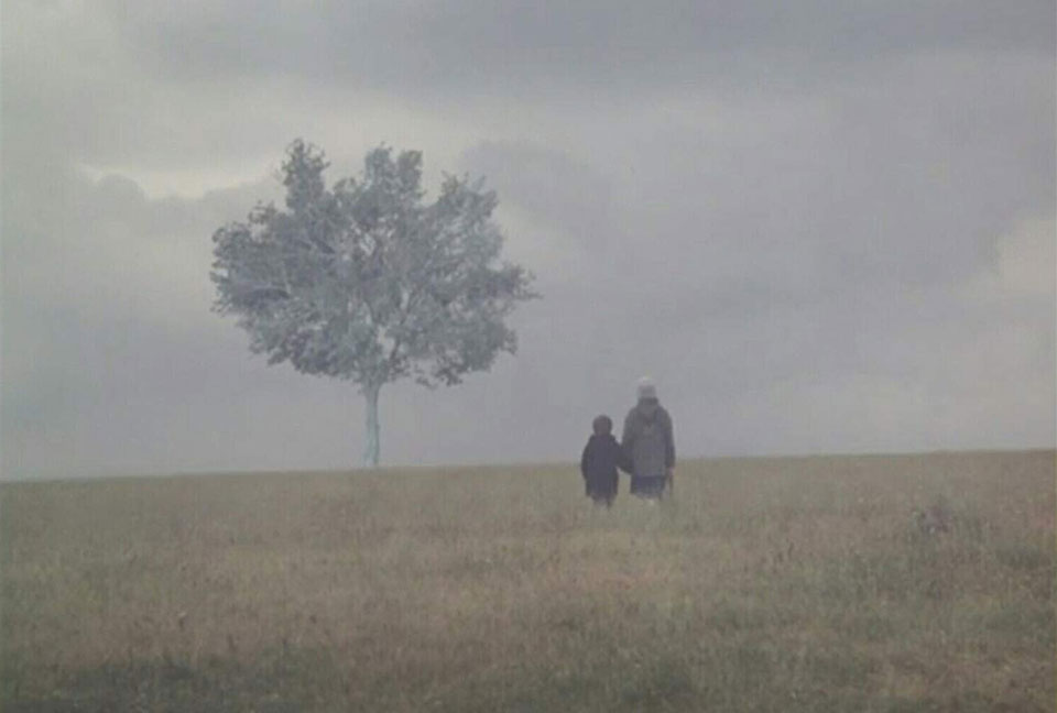 Two figures, presumably parent and child, standing in a gauzy fog, standing in a meadow with a lone tree looming ahead of them