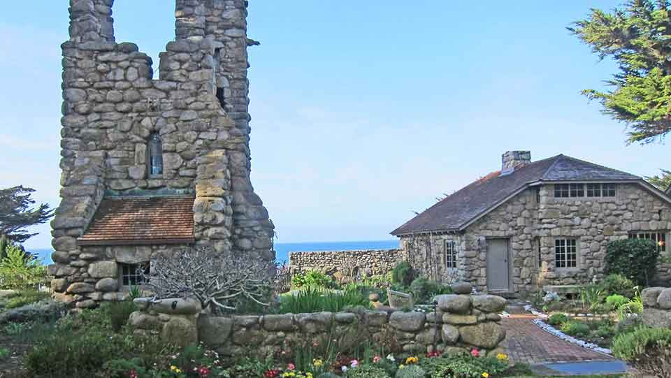 A rugged tower rises to the left of a stone house, both of which sit at the edge of the ocean