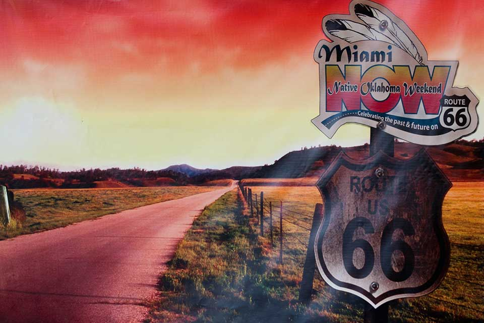 A color-altered photograph (emphasizing red tones) of a highway with a sign beside it in the foreground. The sign reads Route US 66. Another sign has been placed above it that read Miami Now, Native Oklahoma Weekend. Celebrating the past and future on Route 66.