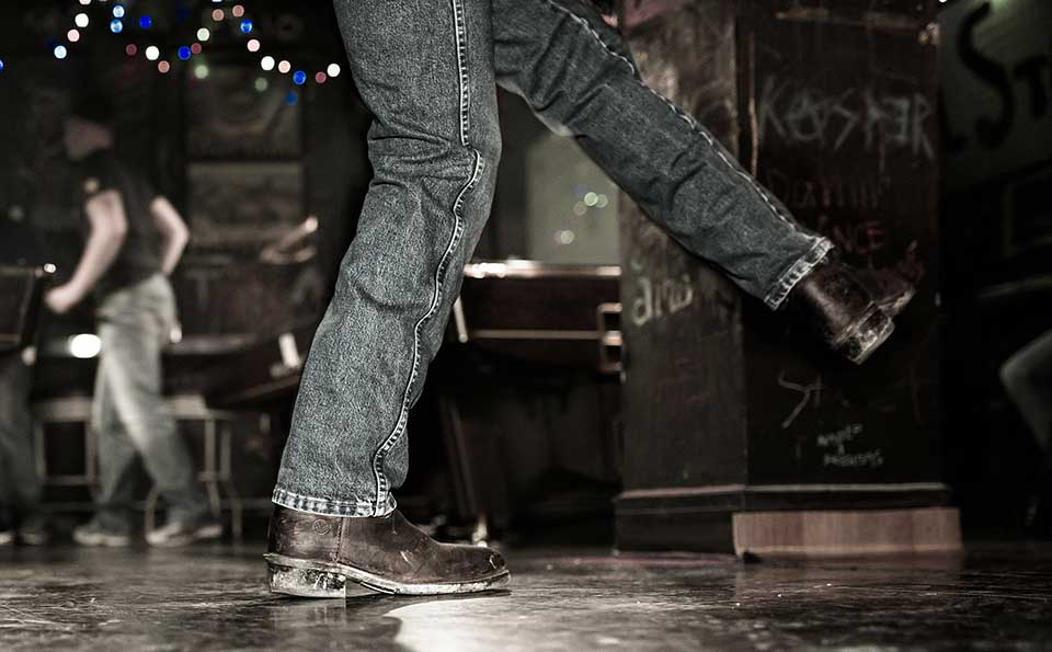 The legs of a dancer, clad in blue jeans and cowboy boots