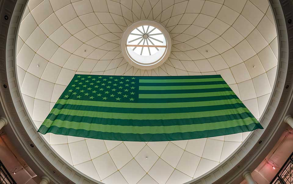 A photograph of an American flag, reimagined in green, hanging from a domed ceiling, as seen from below