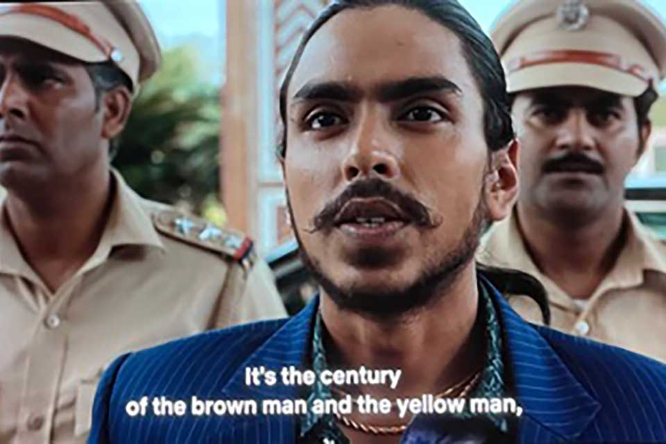 "A still from a movie. A dark-skinned man, dressed in a blue shirt, is flanked on either side by men dressed in military garb. The text (which is a subtitle) reads, ""It is the century of the brown man and the yellow man."""