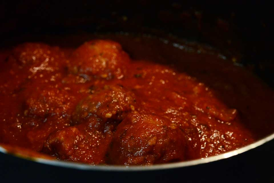 A photograph of meatballs in tomato sauc