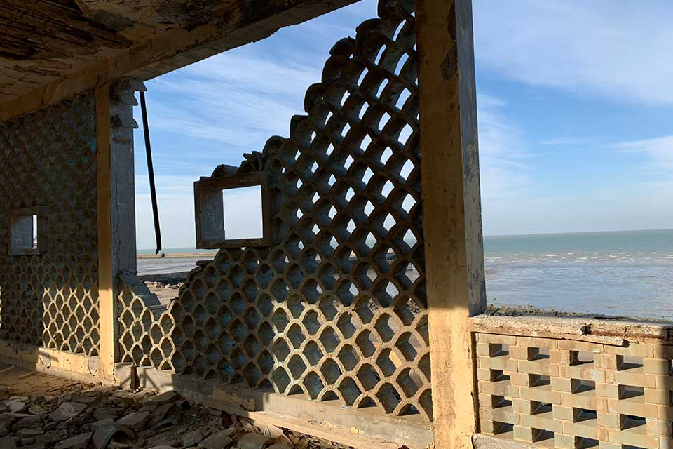 A photograph from inside a crumbling building that looks out toward the sea