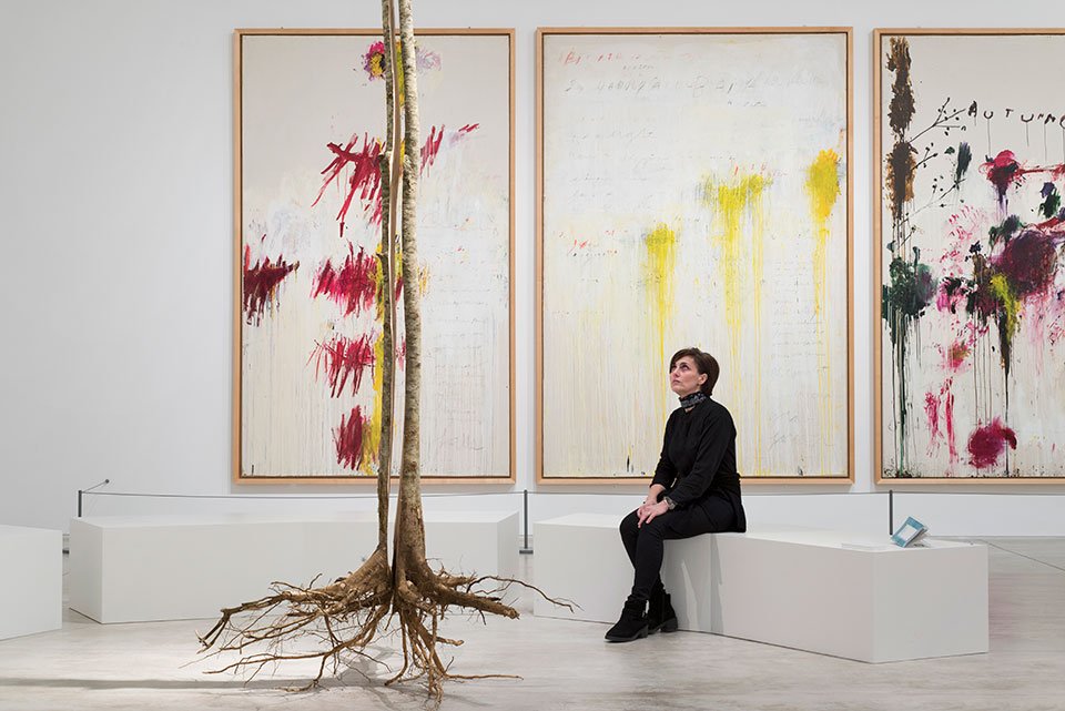 A woman is seated on a stark white bench in front of a triptych of three abstract painting while looking at a tree.