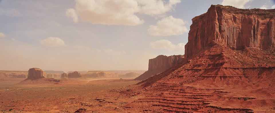 A photograph of a barren Western landscape, with a mesa in the foreground