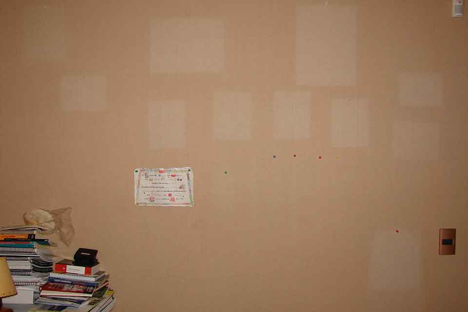 A brown wall with faded spots where pieces of paper where once affixed but have now been removed. A small pile of books and notebooks sits on a table just to the left of the frame