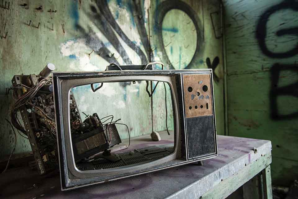 A photograph of a broken television with no screen in a room tagged with graffiti on the walls
