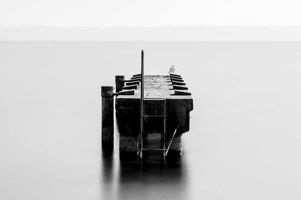 A black and white photo of a small boat dock surrounded by water, which stretches unbroken to the horizon