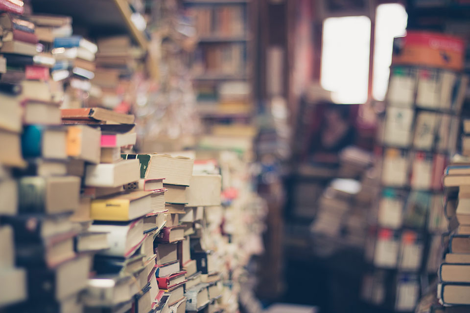 Stacks of books in a room with a window