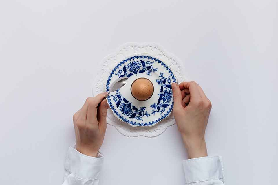 A photo looking down on a single egg on a fine piece of blue china, framed by two hands preparing to eat the egg