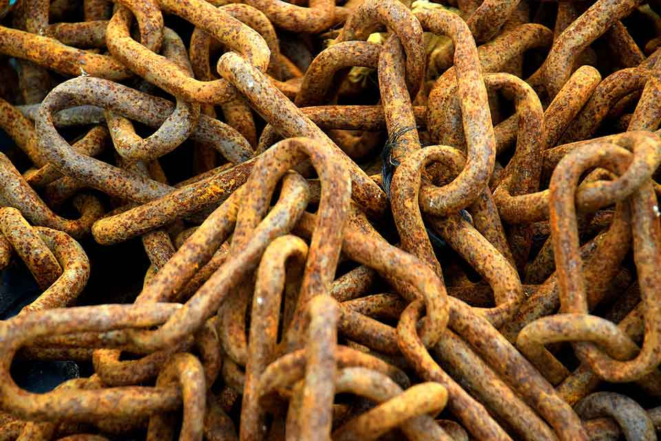 A photograph of a pile of rusted chains