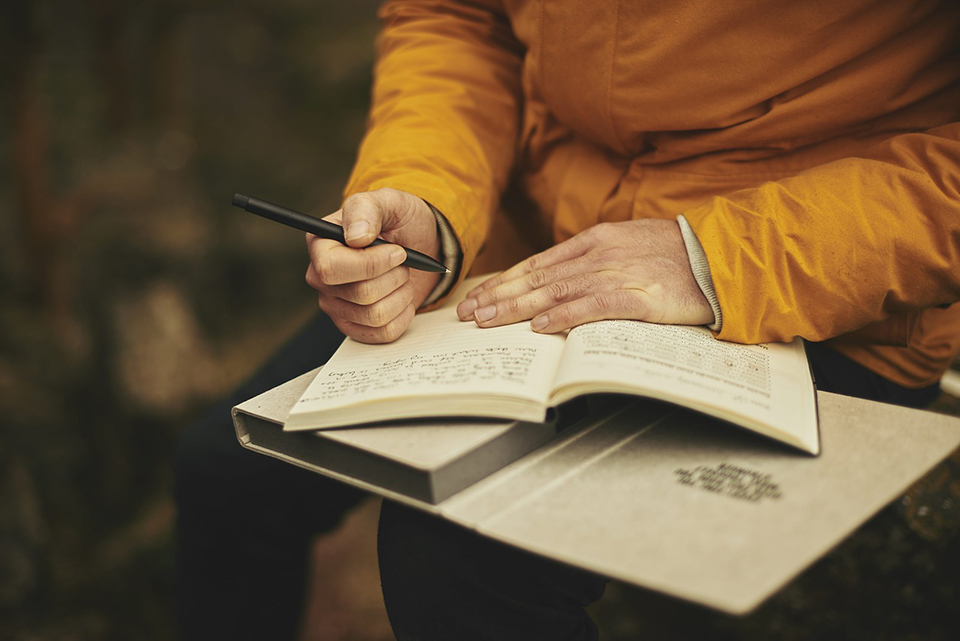 Person in a golden yellow jacket writing in a notebook.