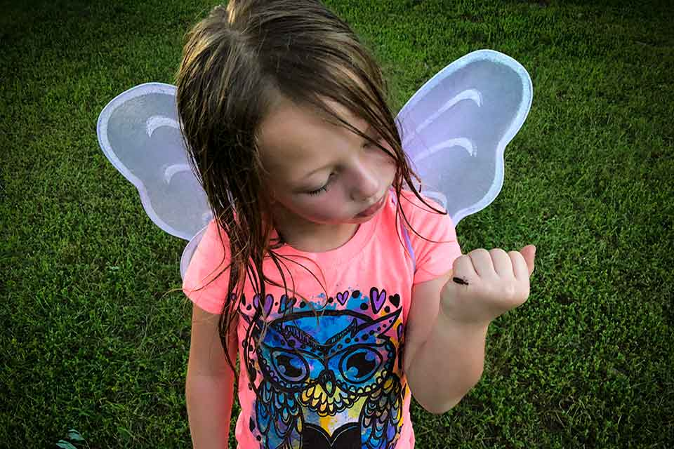 A photograph of a young girl with wet hair in a pink t-shirt. She is wearing a pair of translucent wings.