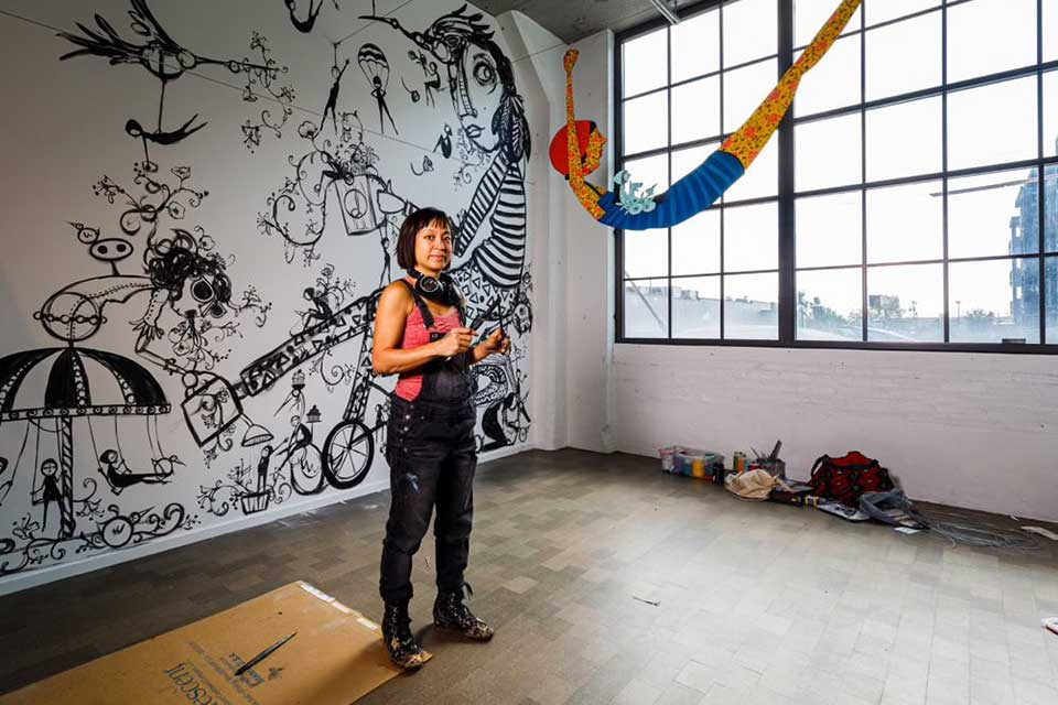 A photograph of Denise Duong standing in an art studio. There are large figures painted on the white wall behind her and the room is lit by large windows on the right.