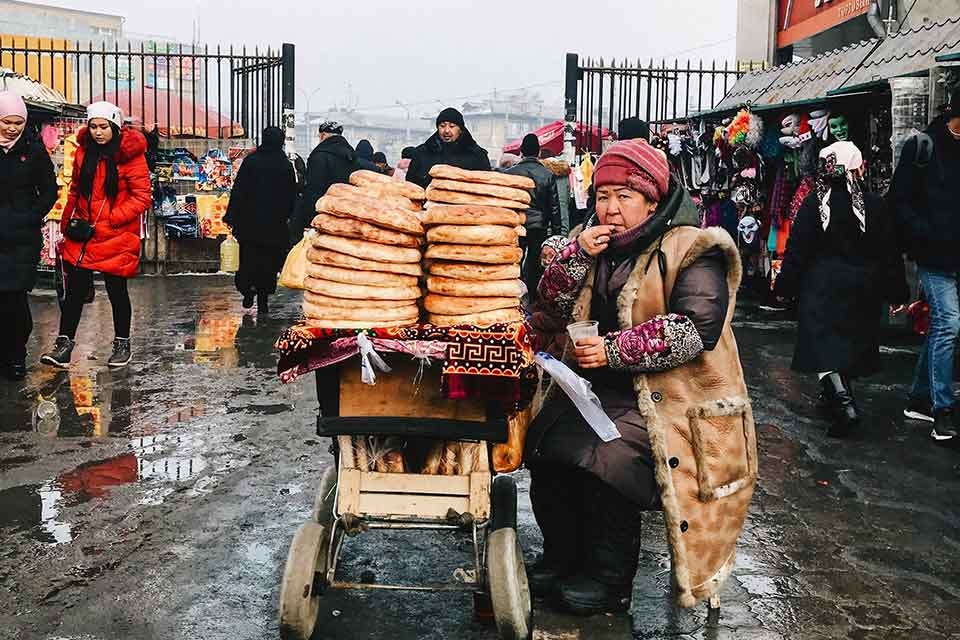 A bread vendor sits next to her piles of bread heaped on a bicycle on a stone plaza in winter
