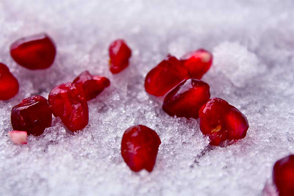 A photograph of dark crimson pomegranate seeds delicately laid out on snow