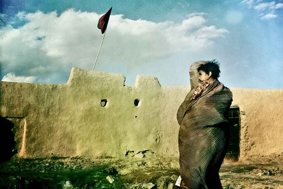A woman veiled from head to toe, holding a child, as she looks at a stone wall with a flag flying above