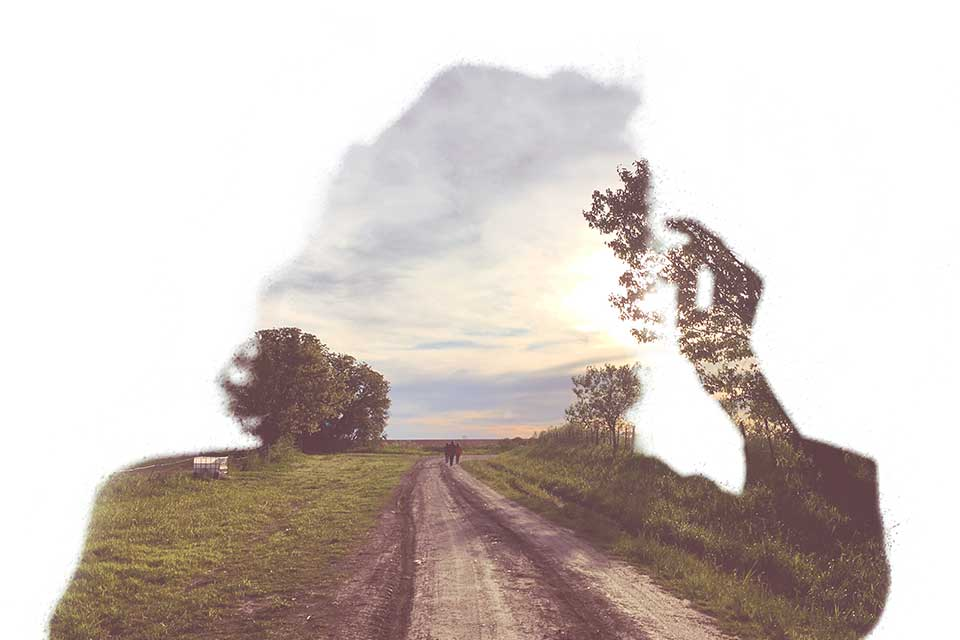 The negative outline of a person blowing on a dandelion through which a photograph of a dirt road stretching into the distance can be seen