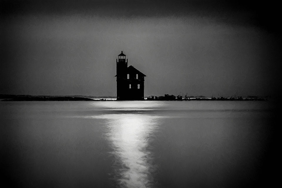 A black and white photograph of a building surrounded by water at night