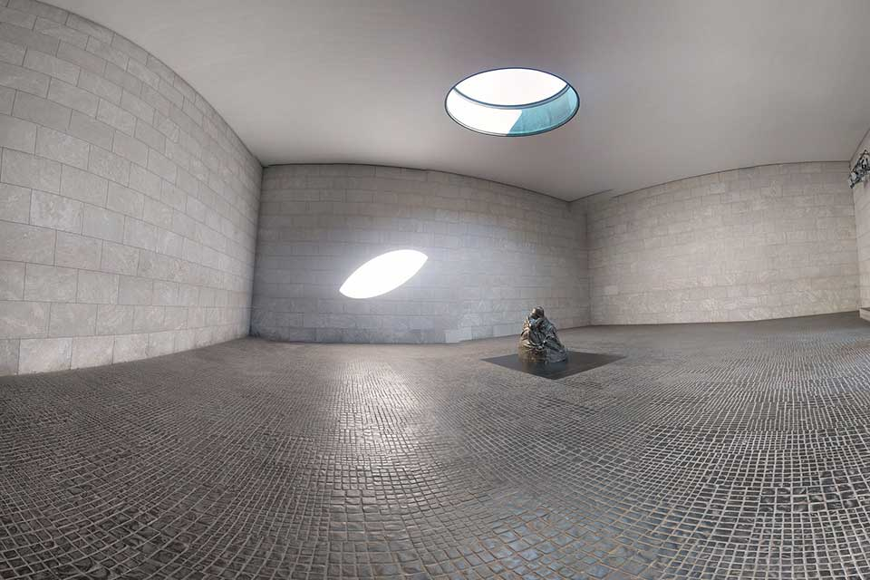 A photograph of a statue of a human figure inside a peculiarly shaped grey room