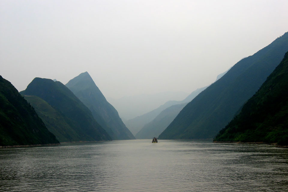 A photograph of a foggy river with a boat visible in the distance