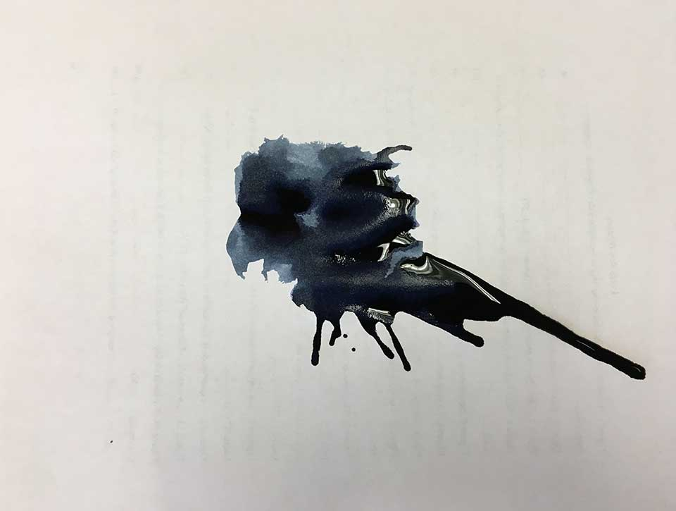 A large inkblot stain on white paper, through which writing on the opposite side just just be seen but not read