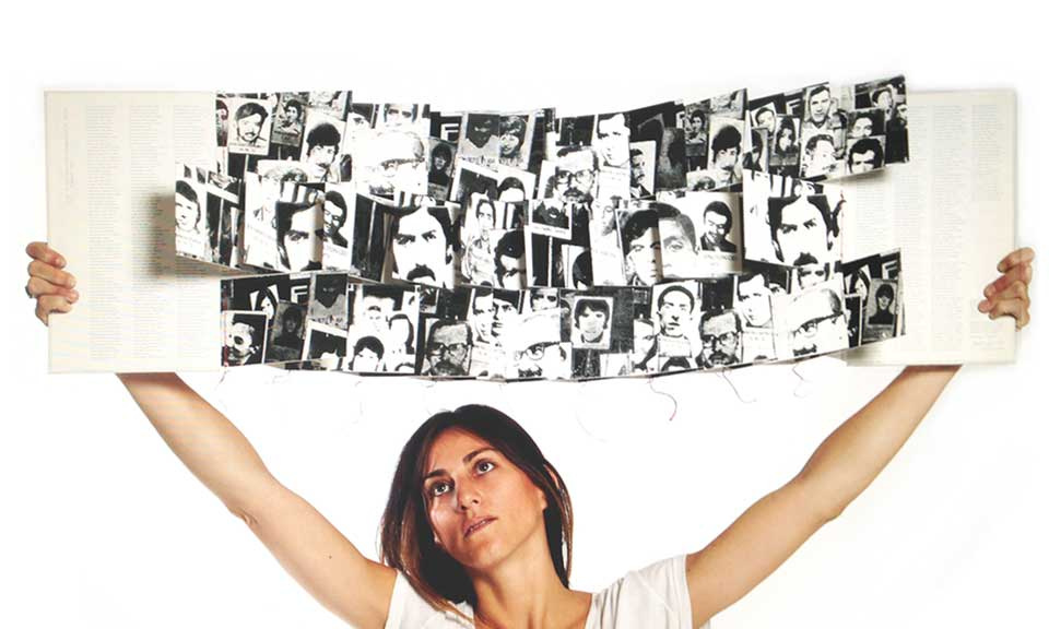 A woman holds up a book filled with illustrations above her head