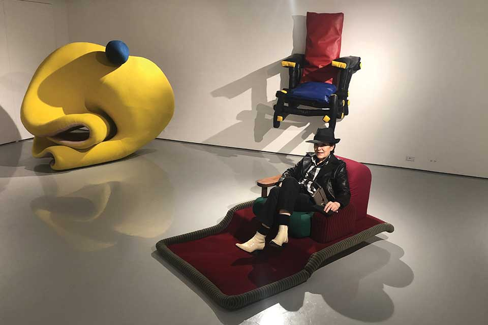 A photograph of Giannina Braschi sitting on a red reclining chair in a gallery space with other unusual furniture displayed