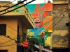 An artist adds color to a building in a Delhi alleyway. Photo by Vikram Singh.