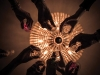 Looking up at a group of hands holding champagne glasses with a chandelier lighted but unfocused in the background.