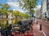A photograph of a row of bikes parked by a canal that runs parallel to a picturesque city street in Amsterdam
