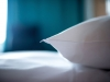 A close-up photo of a white pillow lying on a bed. The blue curtains can be seen, blurred, in the background with a hint of light from the outside streaming in.